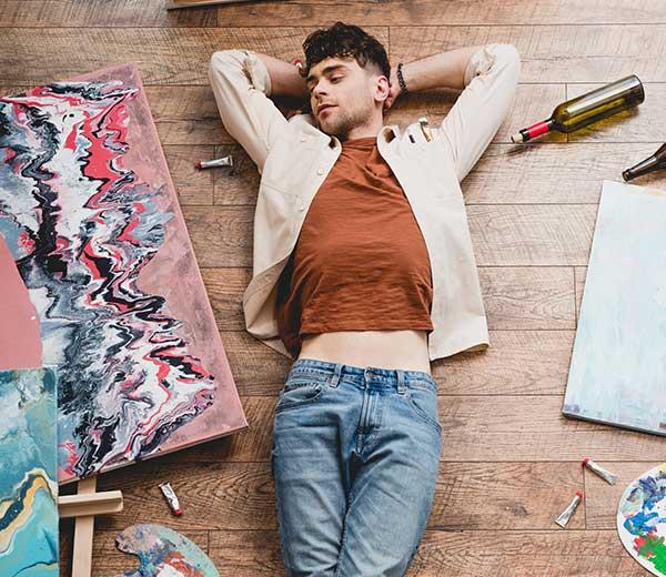 junger Mann liegt auf einem Holzboden von Gemälden umgeben