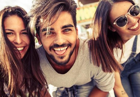 zwei Frauen und ein Mann lächeln in die Kamera