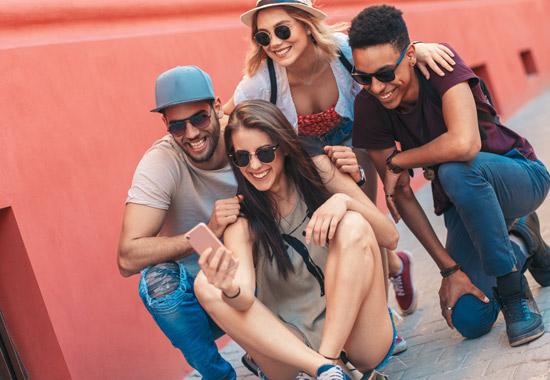 vier junge Menschen mit Sonnenbrille machen ein Selfie im Knien