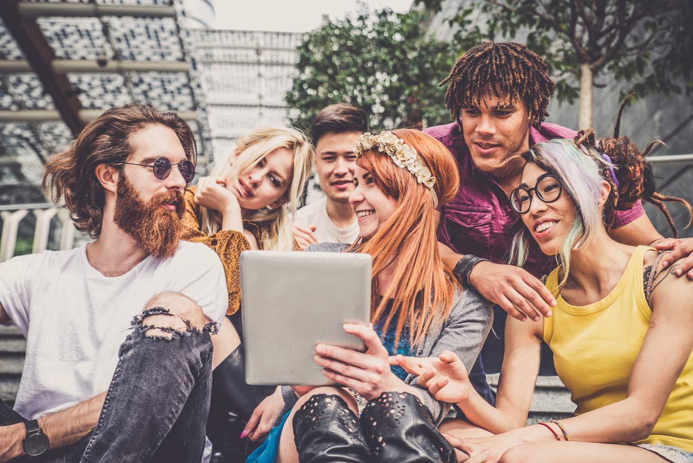 eine Gruppe junger Menschen blickt auf ein Tablet