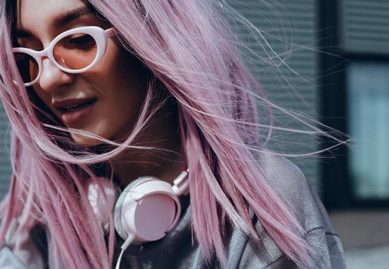 junge Frau mit lila Haaren, weißer Brille und rosa Kopfhören um den Hals
