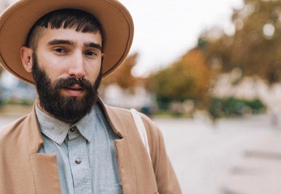 Mann mit Hut, dunkelbraunem Haar und Bart, Nasenring schaut direkt in die Kamera