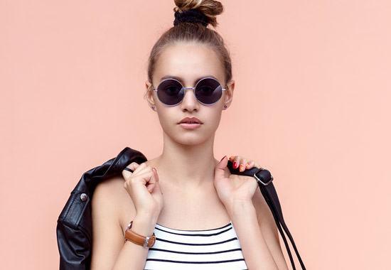 junge Frau mit Dutt und dunkler Sonnenbrille steht vor einer hellrosa Wand