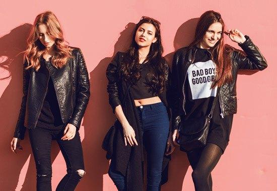 drei junge Frauen mit Lederjacke lehnen sich an eine rosa Wand an